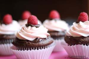 Perfect for Valentine's Day, these decadent chocolate cupcakes are topped with ganache and raspberry buttercream frosting.