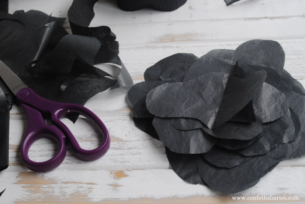 Cut out black tissue paper to make the splotches for the cow print lanterns #barnyardparty