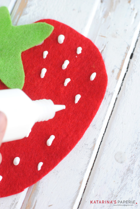 Make strawberry seeds with white puffy paint