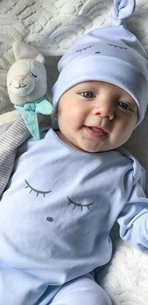 New baby boy dressed in funny blue romper outfit.