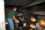 Owner Ernie Schott putting hams on spit at Kennedy's Barbecue