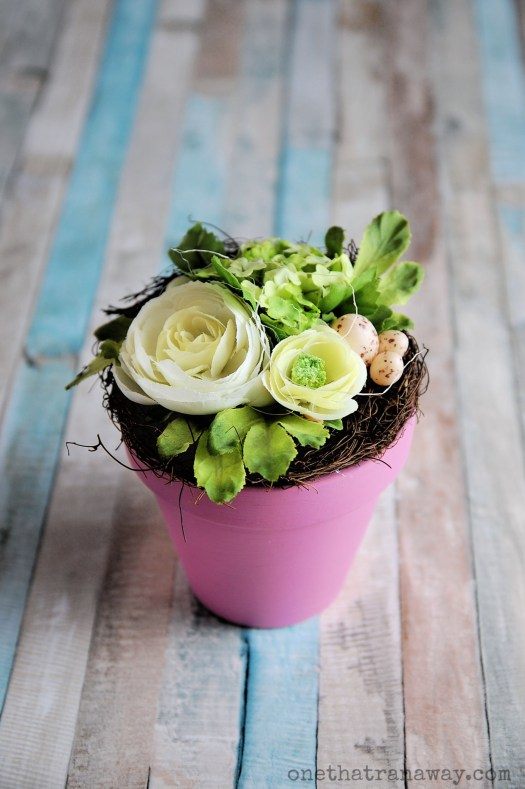 green and cream coloured flower bouquet in a pink flower pot on wooden surface