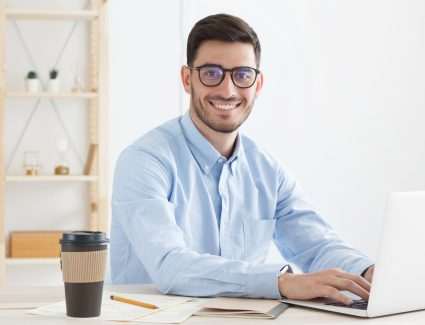 Positive young man wearing glasses and blue t-shirt in office, enjoying time with coffee and work to do on laptop