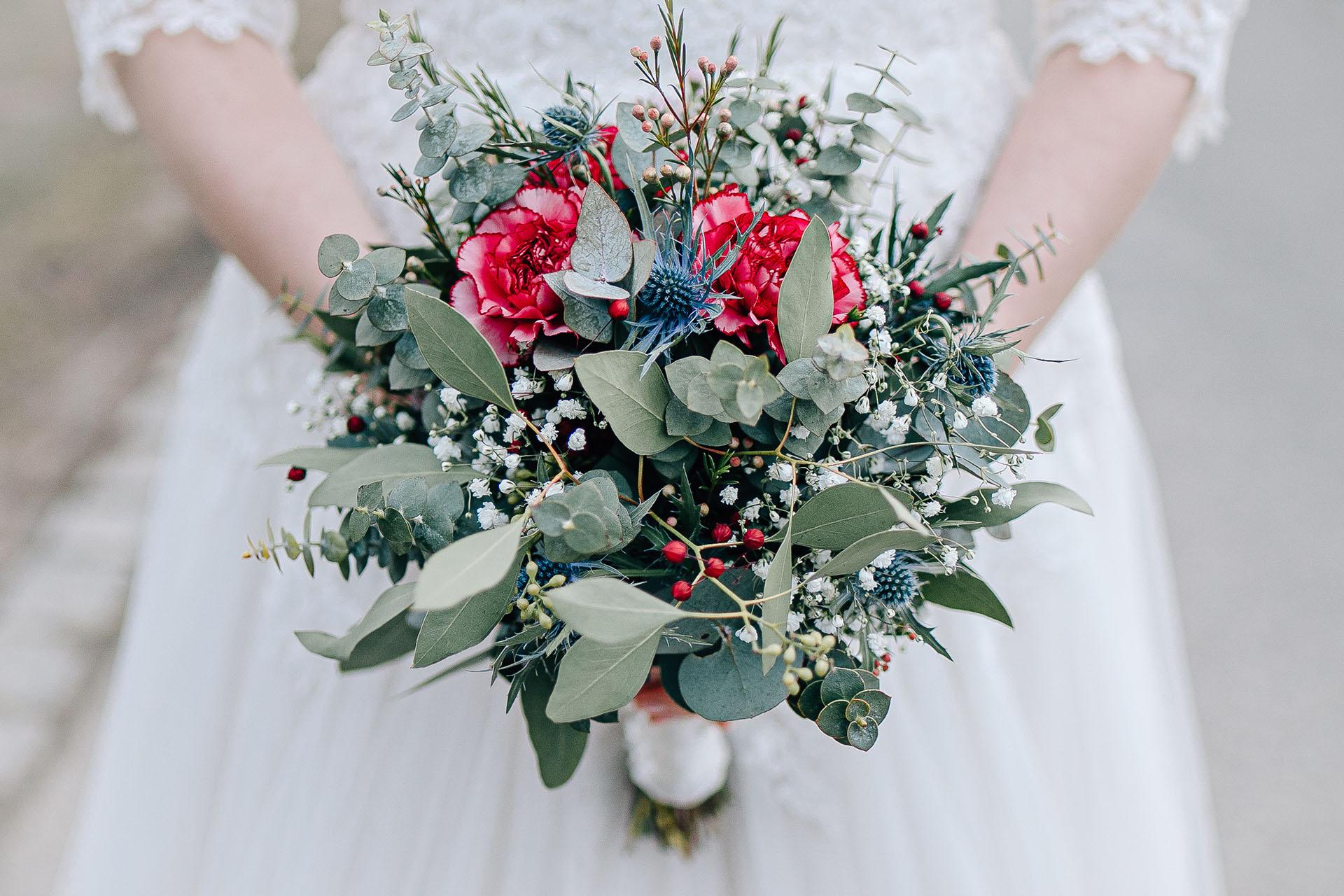 Braut Katharina hält ihren Brautstrauß in beiden Händen.