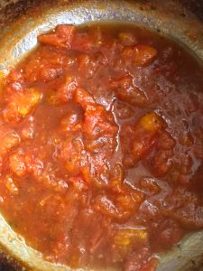 Tomato in tomato sauce while preparation of Uttapam Pizza