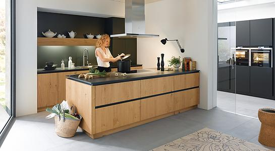 The light oak fronts make the black fronts and countertops equally warmer and more inviting. Especially here are the surrounding recessed grips in the same black tone.