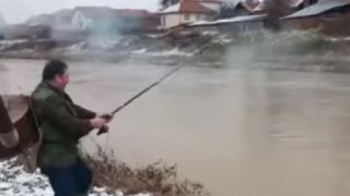 セルビアの漁師のおっさん、寒い日にストーブを背負って釣りをする