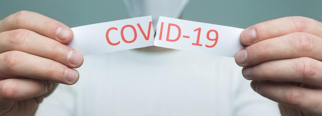 Man wearing a respiratory mask, holding the Coronavirus Covid-19 sign