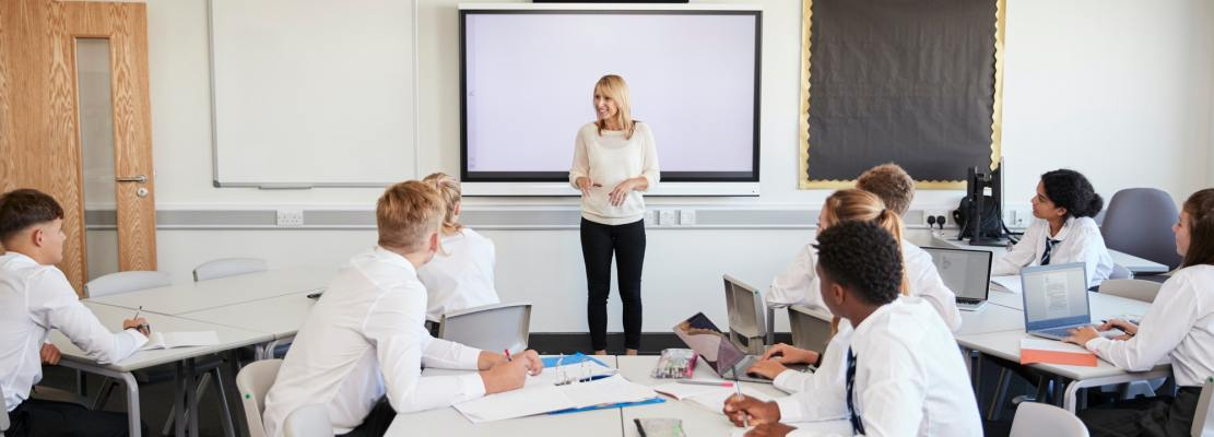 Female High School Teacher Standing Next To Interactive Whiteboard
