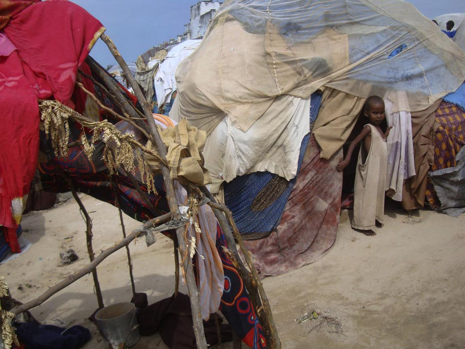 TEMPORARY SHELTER: A Somali girl stood outside a makeshift tent in refugee camp in Mogadishu, Somalia, Thursday. The United Nations estimates that tens of thousands of people have died from malnutrition in Somalia in recent months. (Farah Abdi Warsameh/Associated Press)