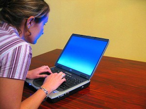 A woman typing on a laptop