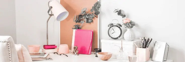 pretty desk with lamp, clock and plants