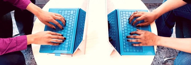 two people typing on blue laptops