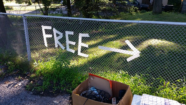 An errow on a fence and a sign saying free.