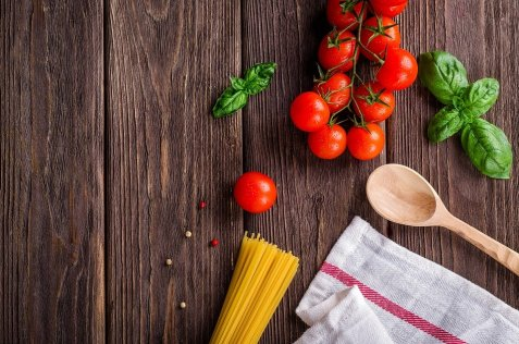 pasta, tomatoes, and basil laid out next to a kitchen towel and a wooden cooking spoon.