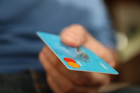 a light blue credit card being used while attempting to live cheap in Manhattan.