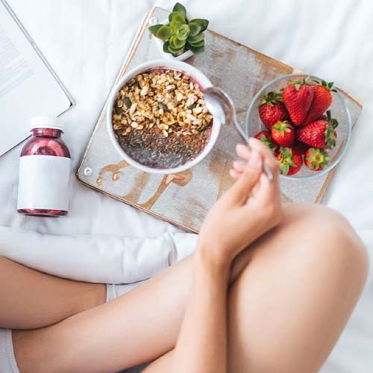 woman eating breakfast of yogurt cereal and strawberries in bed