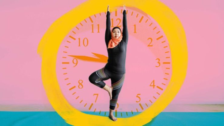 A woman exercises in front of an image of a clock to depict how to stick to fitness goals and daily exercise habits.