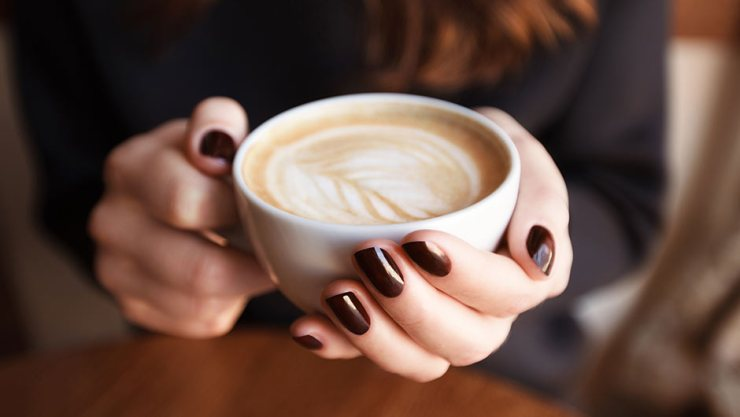 woman holding latte with latte art
