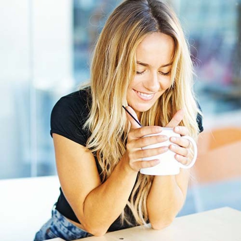woman leaning on counter drinking coffee out of mug