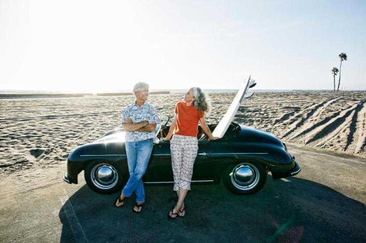 Older Caucasian couple leaning on convertible car with surfboard on beach