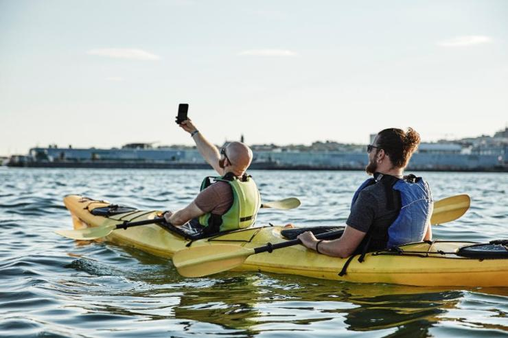 Photograph of man taking selfie in tandem sea kayak, Portland, Maine, USA