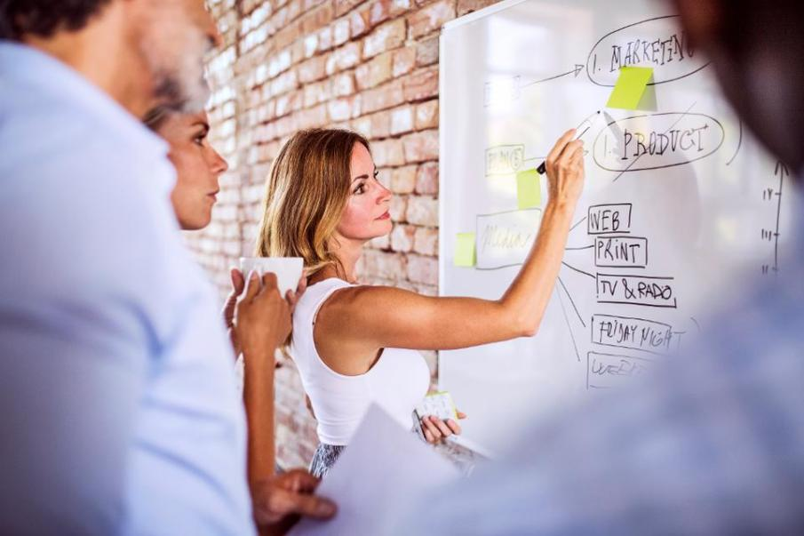Business team working together on whiteboard at brick wall in office