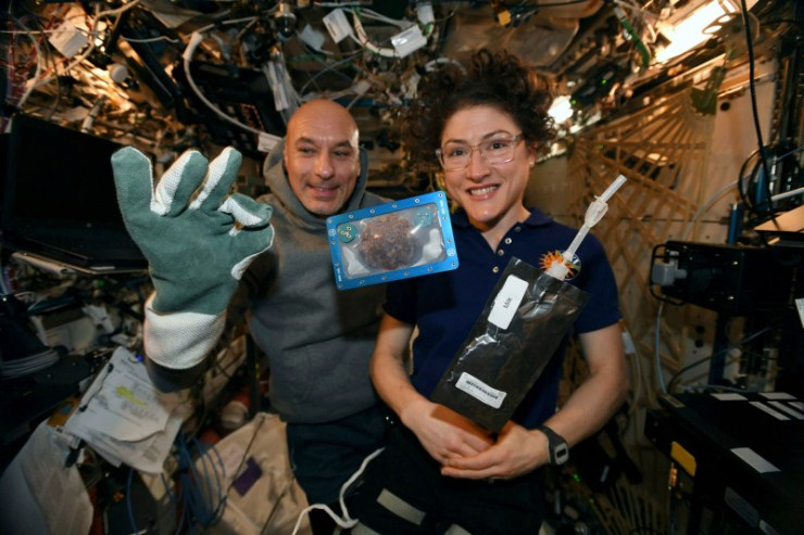 In this photo made available by U.S. astronaut Christina Koch via Twitter on Dec. 26, 2019, she and Italian astronaut Luca Parmitano pose for a photo with a cookie baked on the International Space Station.