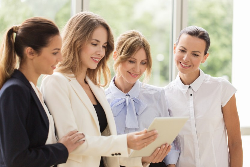 people, technology, work and corporate concept - business team of women with tablet pc computer at o