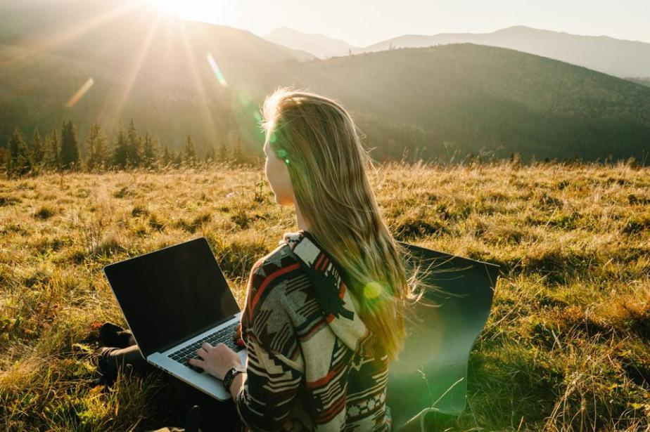 Woman traveler using laptop computer while enjoying sunset in mountains. Freelancer girl working on netbook during vacation holidays in autumn. Distant work and travel, freelance as lifestyle concept.