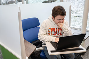 Male student working on a laptop