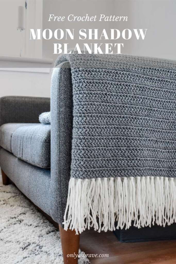 A pinterest pin showing a grey herringbone stitch crochet blanket with cream tassels folded over the end of a sofa
