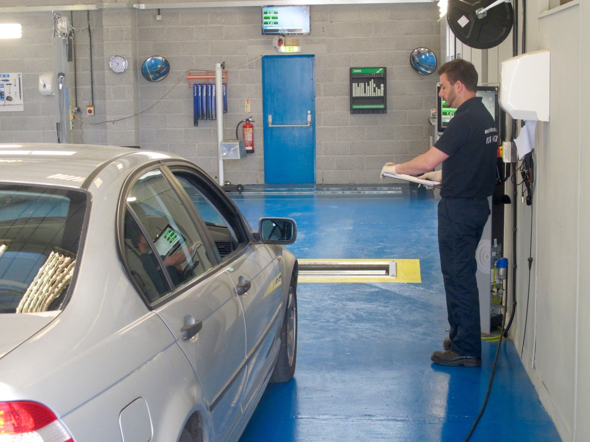 Mot tester standing by car with a clipboard during MOT inspection