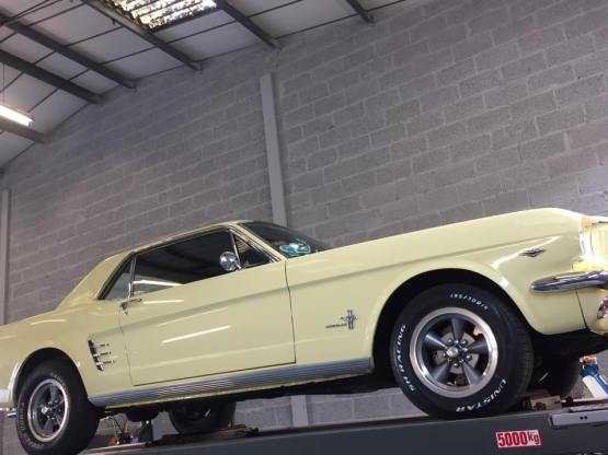 Gallery of images classic vintage car in cream on a ramp at an MOT testing facility