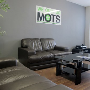 Gallery of images waiting room with brown leather sofas, coffee table and sign saying we only do mots