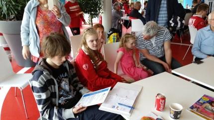 Kids kijken naar hun brevet met trotse ouders en opa's/oma's om hen heen