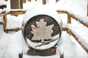 Tonneau avec une feuille d'érable sous la neige au Québec