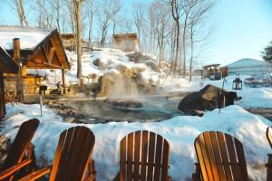 Un bassin d'eau chaude sous la neige dans le Nordik Spa-Nature au Québec en hiver
