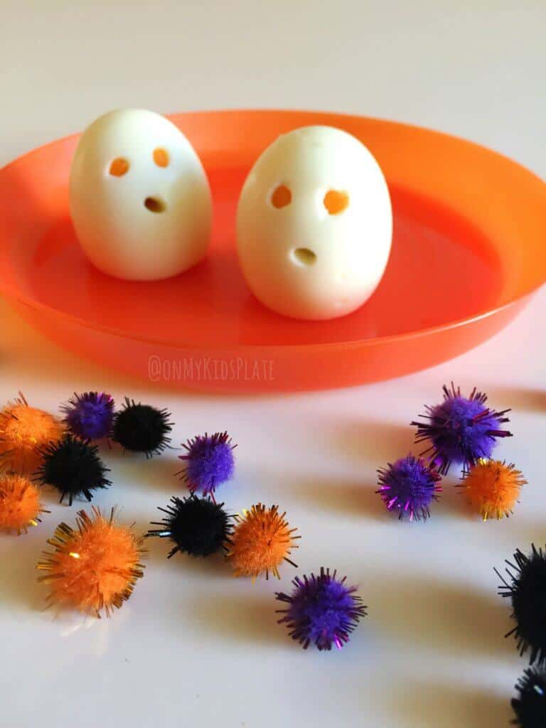Two hard boiled eggs on a plate made too look like ghousts with eyes and a mouth cut out for a fun snack.