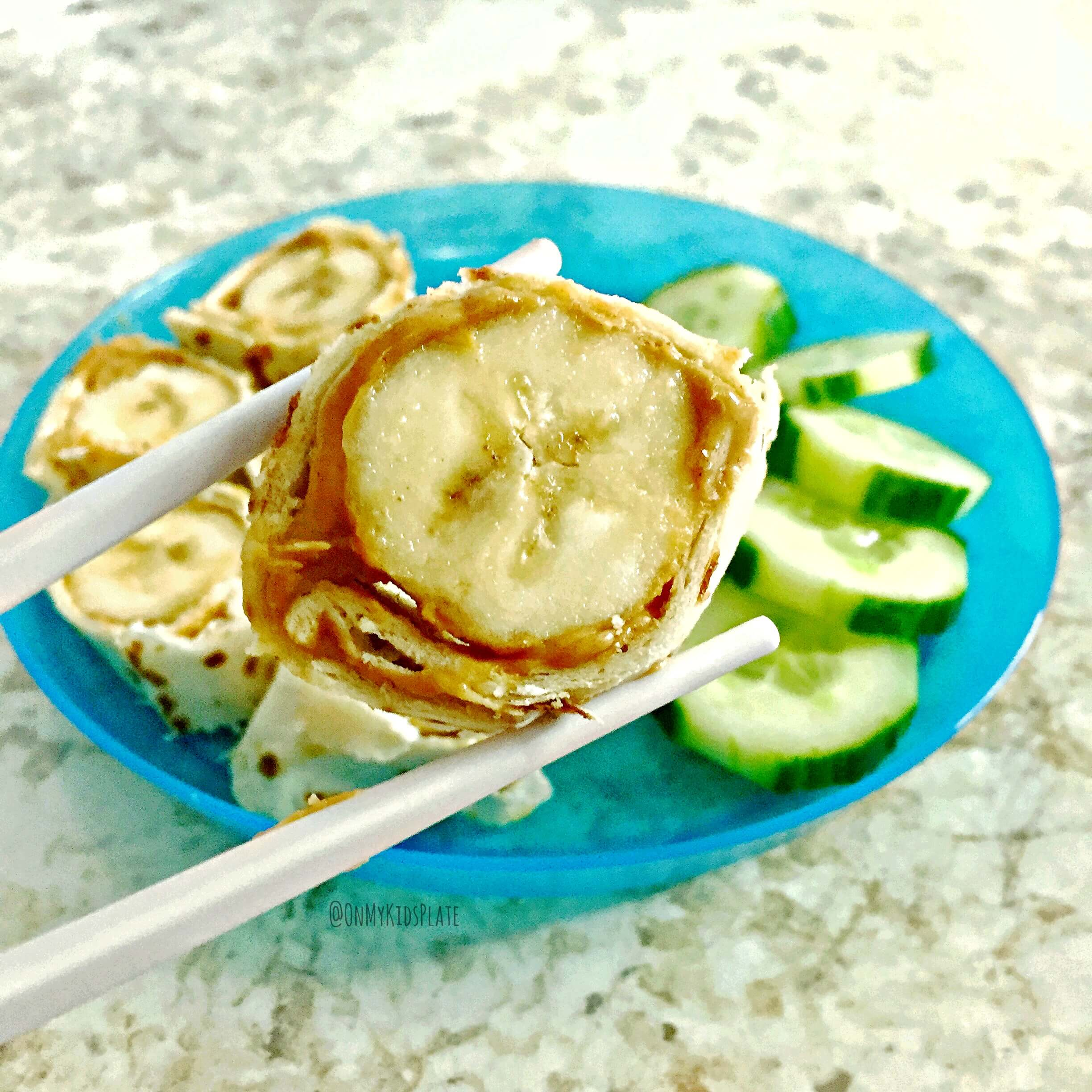 banana sliced with peanut butter wrapped in tortilla on a plate with sliced cucumber, one slice being held by chopsticks