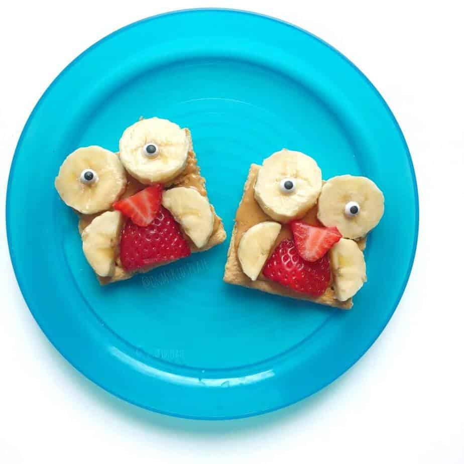 Two graham crackers on a plate decorated with fruit to look like owls