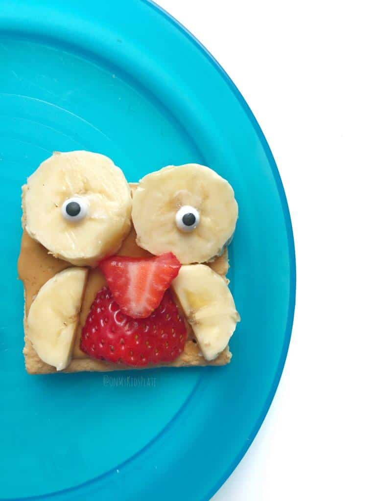 A graham cracker decorated with fruit to look like an owl on a blue plate