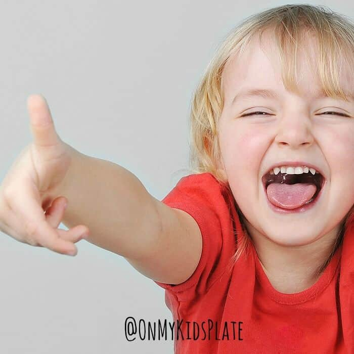 A small child holding her thumb up laughing