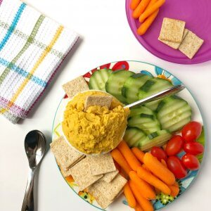 A platter of yellow dip with sliced vegetables and a child's plate with food ready to eat.