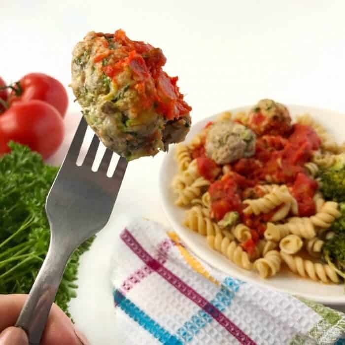 A meatball on a fork, a plate of pasta with meatballs int the background