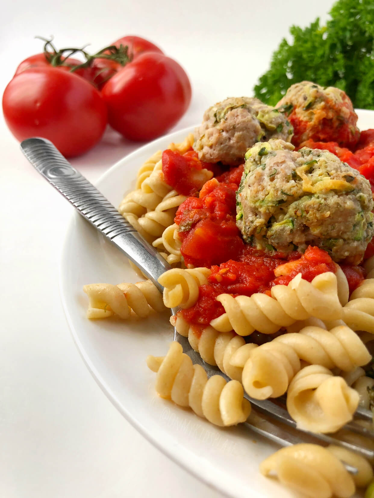 A plate of meatballs, pasta and tomato sauce with tomatoes and parsely in the background