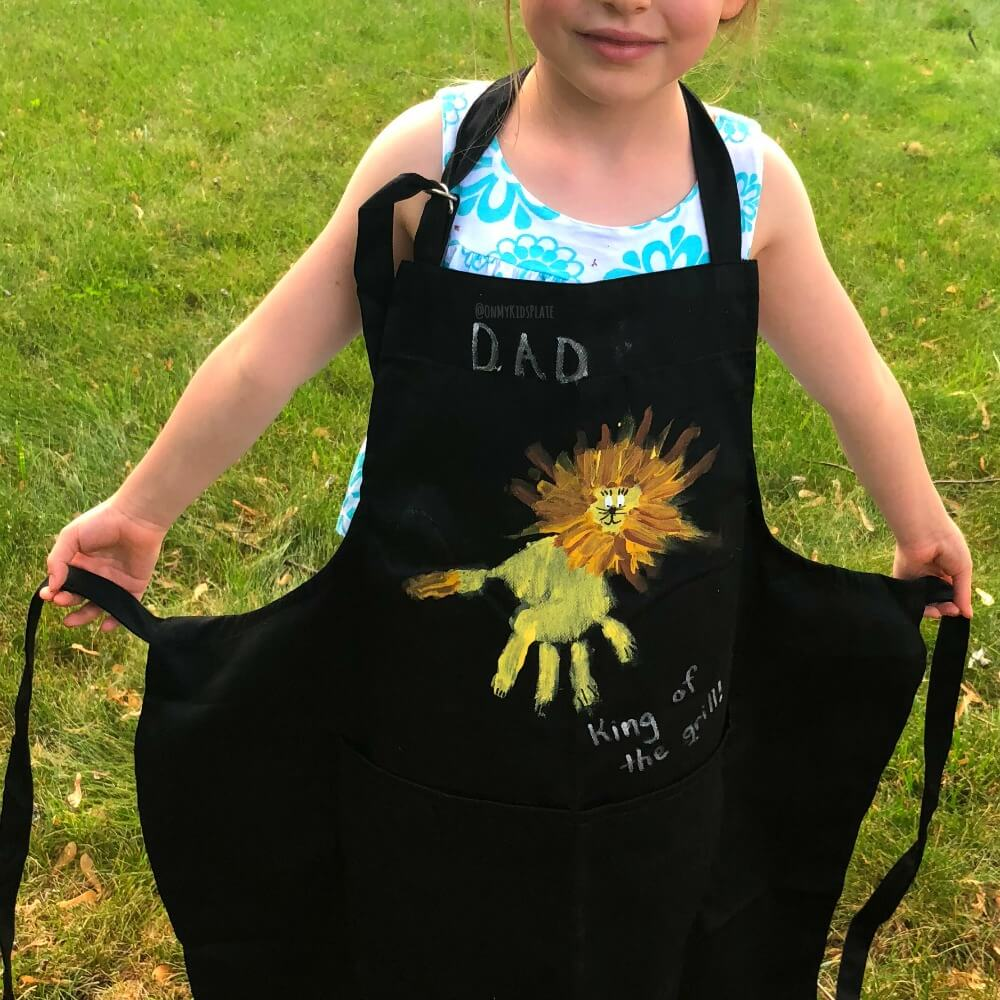 A child wearing an apron decorated for dad with lion shaped handprint art