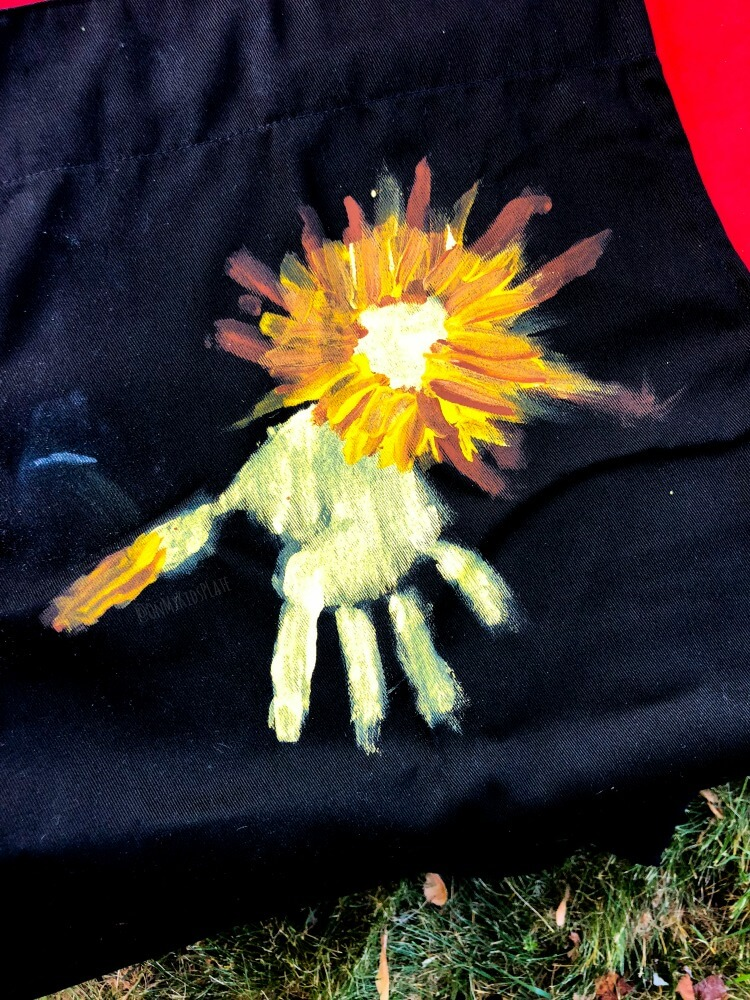 On a black grill apron we see a child's painted handprint made into the shape of a lion.
