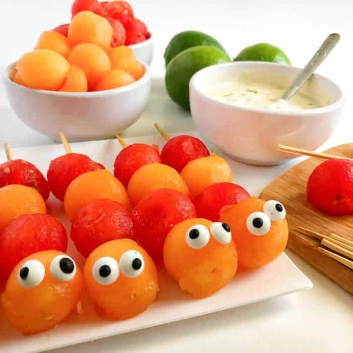 Melon balls decorated to look like caterpillars on sticks with more fruit and yogurt behind