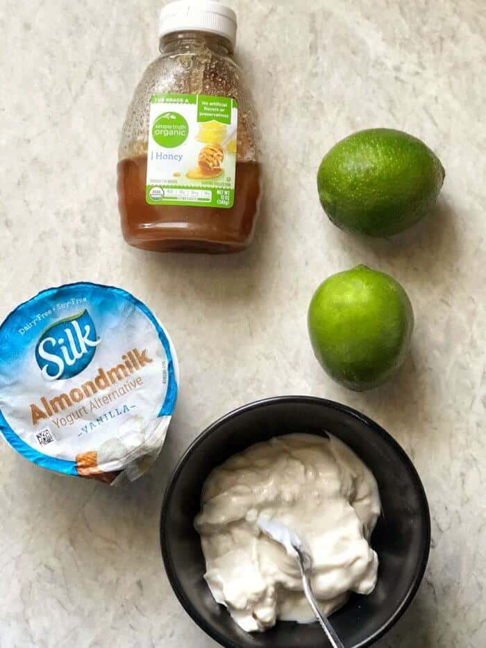 Yogurt, limes and honey with ingredients mixed together in a bowl.